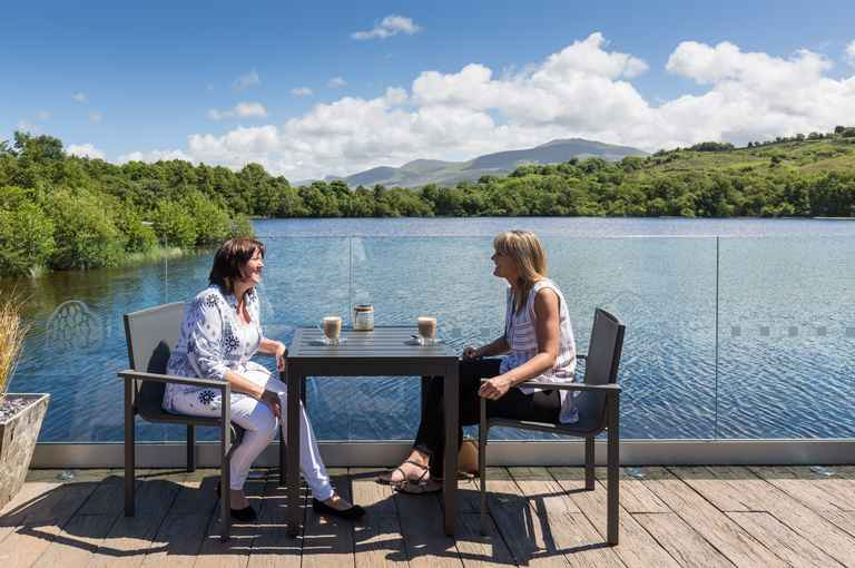 two women drinking coffee by the lake at brynteg coastal & country retreat in snowdonia