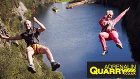 two people hanging in harnesses over a lake at adrenaline quarry in cornwall