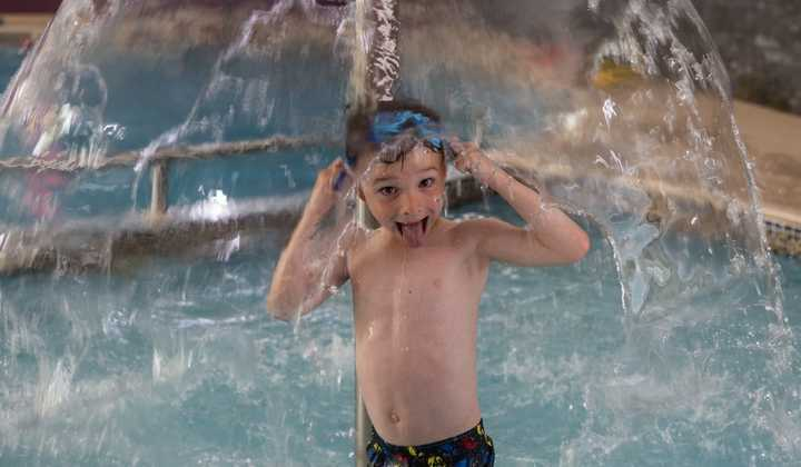 Young boy in swimming pool at brynteg holiday park in snowdonia wearing goggles under a fountain