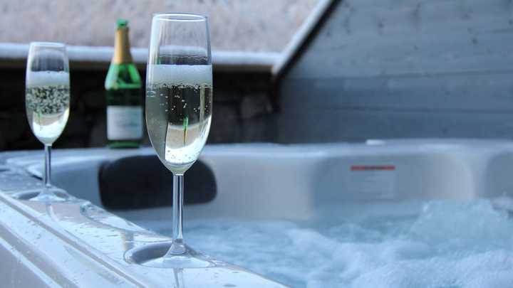champagne glasses and bottle atop a bubbly hot tub