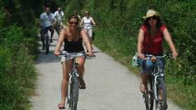 two people cycling along a path in cornwall