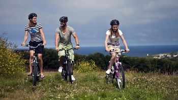 three friends cycling in cornwall by the sea