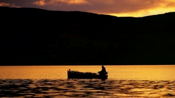 silhouette of fishermen on his boat at sunset