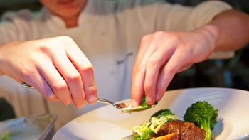 chef placing finishing touches on a plate of food