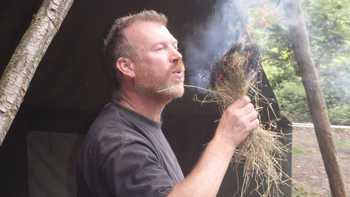 man blowing oxygen into dry grass fire at survival activity camp