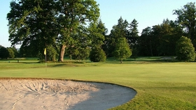 scenic golf course surrounded by trees with sand bunker
