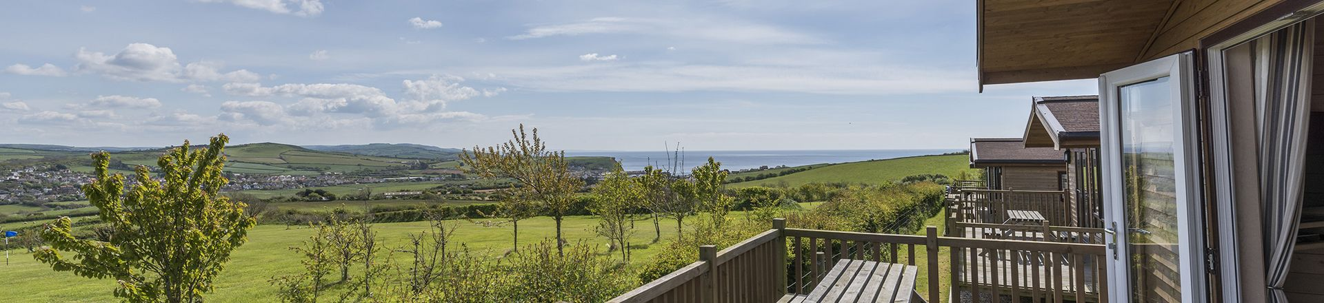 row of lodges with beautiful countryside and sea views at highlands end holiday park