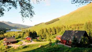 Lodges in Perthshire, Scotland on a hillside in the sunshine with the mountains and lake in the distance