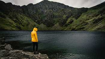 person in raincoat stood looking at lake on a stormy day in Snowdonia, Wales