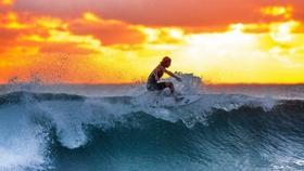 surfer riding the waves at sunset